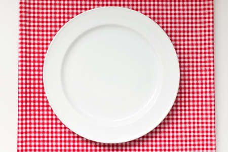 white red: white dish or plate on red classic checkered tablecloth texture on white table with copy space for advertise food product and other Stock Photo