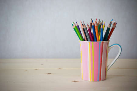 Still life color pencils in colorful cup on wooden table - vintage effect style picture