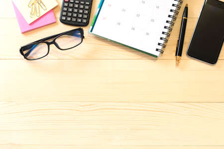 Office table with notepad, calculator, glasses, post it, pen and smartphone. View from above with copy space Stock Photo