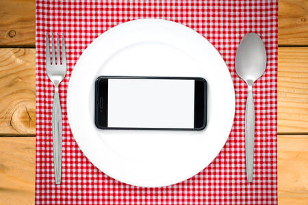 food absorption: Smartphone on white dish or plate between spoon, fork on red classic checkered tablecloth texture on wooden table with copy space for advertise food product and other