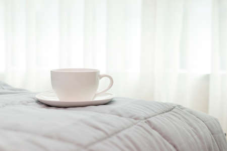warm drink: coffee cup in the morning on the bed background