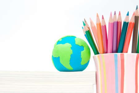 environmental education: Globo de la tierra hecha de arcilla en la pila de libros y l�piz del color en taza de colores. La conciencia ambiental y el concepto de la educaci�n Foto de archivo