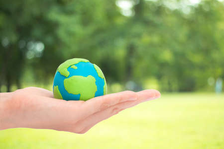 green world: human hands holding planet or earth over blurred green garden nature background. Ecology concept. Stock Photo