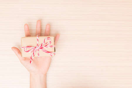 hold hands: Hands holding gift on wooden table. Stock Photo