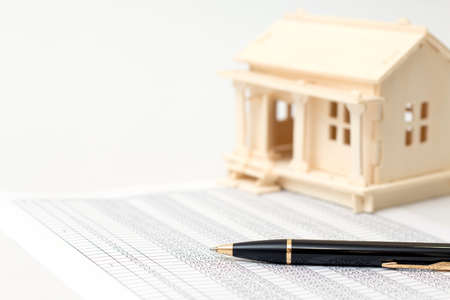 home loans: House wooden and pen for Home loans concept