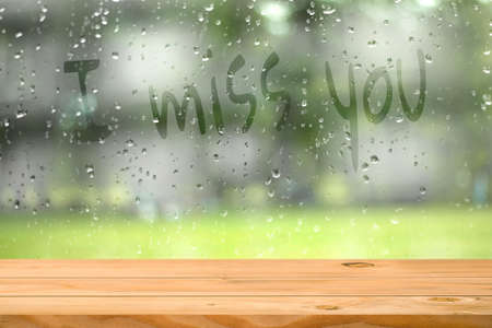 Empty wooden table near water drop on window with wording i miss you blurred garden background. Ready for product display montage. Love and lonely Concept.