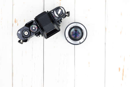 old photo: Top view of old camera body and len on white wooden background with copy space