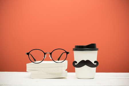 橙色复古背景的木桌上放着书、眼镜和有胡子的杯子
