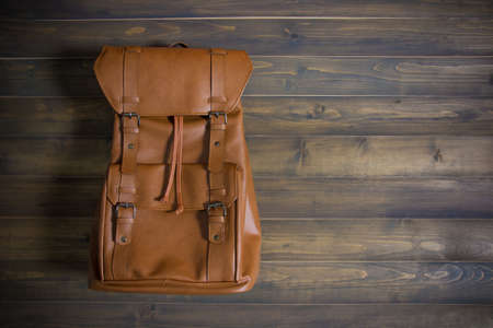 leather texture: Brown leather bag on wooden table. Top view. Travel concept.