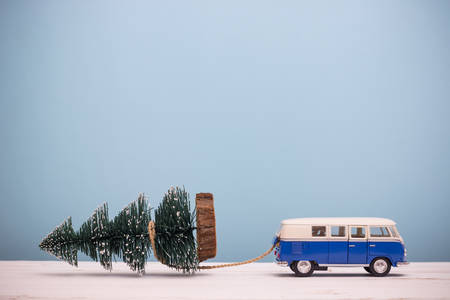 Miniature figure toy car drag Christmas tree on wooden table blue background, Image for Christmas Holiday decorative concept.