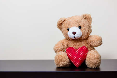 bear doll and red heart on wooden table Stock Photo
