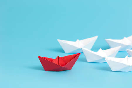 Leadership concept with red paper ship leading among white on blue background with copy space. Business leadership concept. Minimal style. Stock Photo