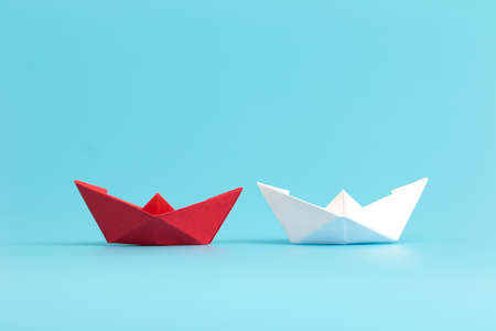 Two paper boats competing. Business competition concept. Minimal style. Stock Photo