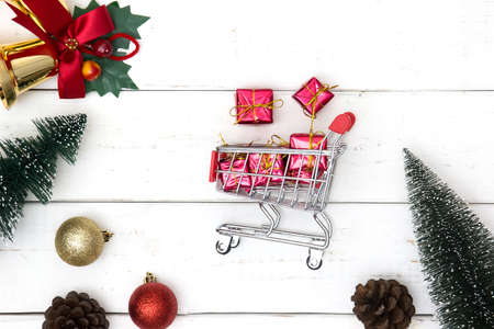 holiday shopping and christmas gift exchange concept with shopping cart and xmas decorations on wooden white