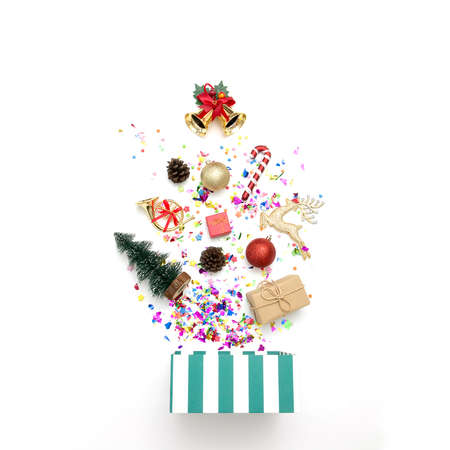 Gift box with various party confetti and christmas decoration on a white background. Colorful celebration background.