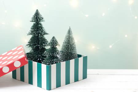 크리스마스 트리를 통해 나무 테이블에 선물 상자 흐림 bokeh 밝은 녹색 배경, 크리스마스를위한 이미지 휴일 장식 개념입니다. 최소한의 개념.