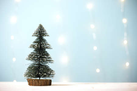 Miniature christmas tree on wooden table over blur bokeh light blue background, Image for Christmas Holiday decorative concept. Minimal concept. Stock Photo