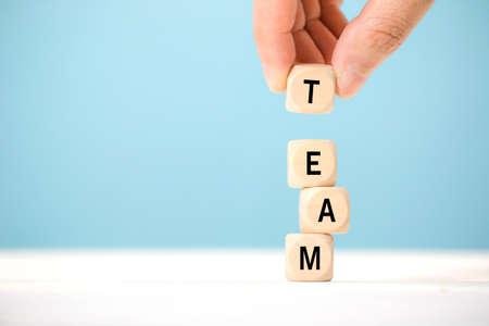 手は、チームを表す木製のテーブルの上に文字と木製の立方体要素を保持します。ビジネスコンセプト。