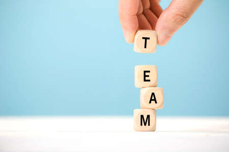 Hand hold wooden cube elements with letter on wooden table, which represents team. Business concept.