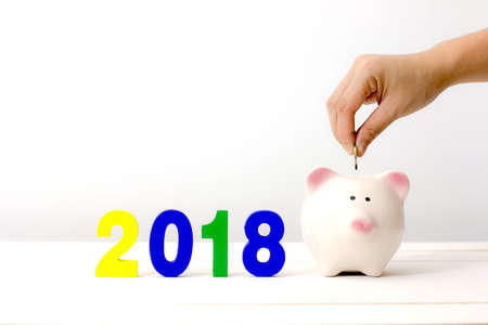 Human hand putting coin into a piggy bank and colorful wooden number 2018. Happy new year 2018 and Saving concept.
