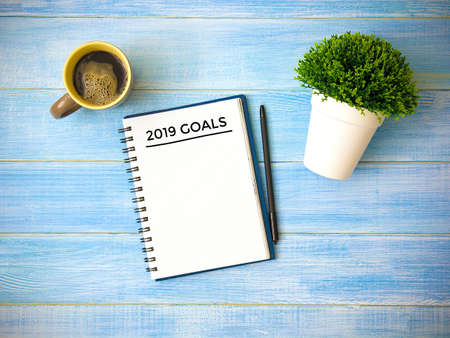 Top view of notebook handwriting goals for 2019 year, cup of coffee on blue wooden table. Business plan concept. 写真素材