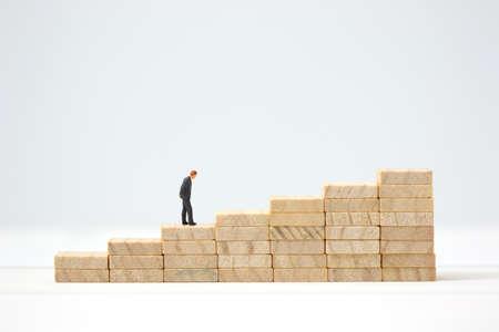 Miniature businessman making the decision on wooden graph. Business goal achievement concept. 免版税图像