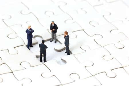 Miniature businessman meeting about lost jigsaw one piece. Business solution and teamwork concept. Standard-Bild - 115428482