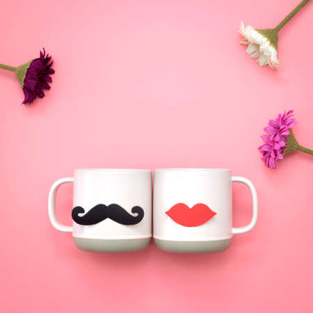 Flower and paper heart shape fake lips and mustaches decoration on pink cup over pink background. Valentine's day and wedding concept. Minimal style. Stockfoto