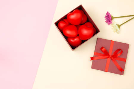 Flat lay of red heart in gift box and flowers on pink and yellow pastel background with copy space. Love and Valentine's day concept. Minimal style.