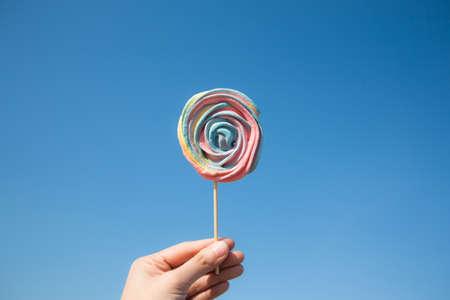 Lollipop candy on blue sky background. Hipster food summer concept.
