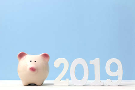 Pink piggy bank with wooden white number 2019 on table and blue soft pastel background. Happy New Year 2019 financial concept.