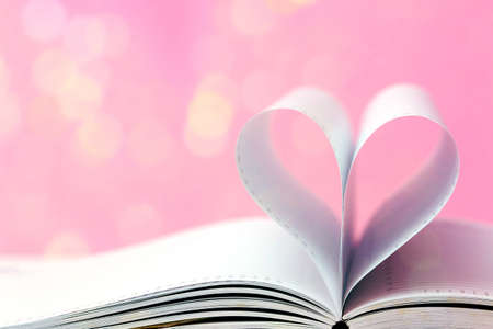 Open book with heart shape on light bokeh pink background. Valentine's day concept. Minimal style.