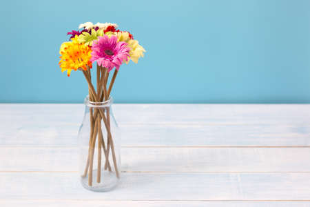 Colorful flowers bouquet in clear bottle on light blue table in front of blue wall. View with copy space