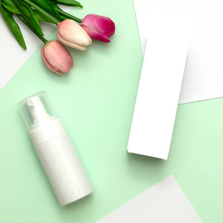 White cosmetic products and pink tulip flower on mint green and white paper background. Natural beauty products for branding mock-up concept. Stock Photo