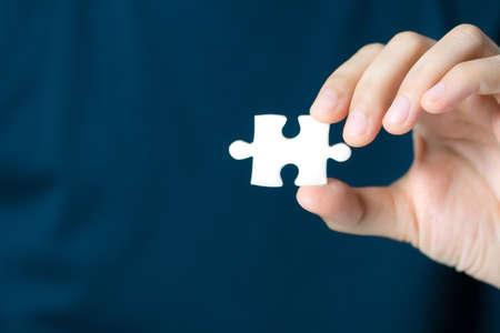 Hand showing blank jigsaw puzzle piece for insert wording. Business presentation concept. Stock Photo