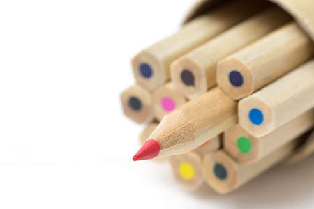 Red pencil standing out from crowd on white table. Leadership, uniqueness, independence, initiative, strategy, dissent, think different, business success concept.