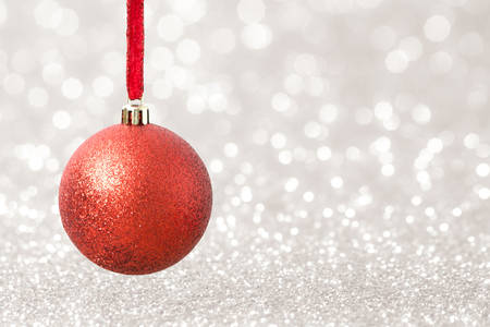 Christmas bauble decoration on bright bokeh light blurred background. Holiday concept.
