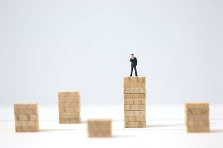 Miniature businessman making the decision on highest wooden stacks. Business goal achievement concept. Stock Photo