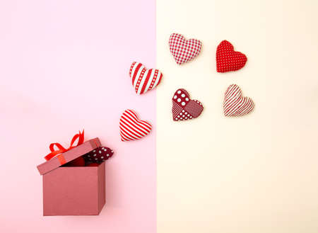 Pillow balloon hearts floating out of the gift box. Creative thinking about love and Valentines day. Minimal style. Stock Photo
