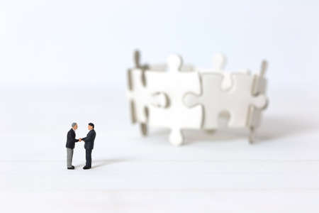 Miniature businessmen shaking hands  on blurred group of jigsaw puzzle background. Concept of partnership successful.