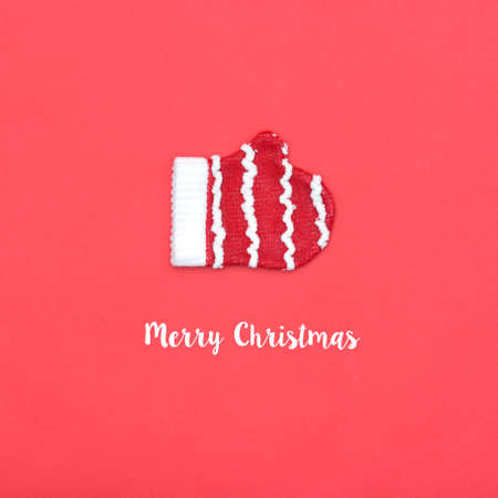 Santa Claus glove flat lay on red background with word merry christmas. Minimal style. Holiday concept.