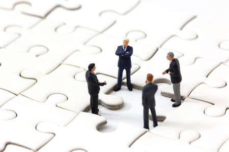 Miniature businessman meeting about lost jigsaw one piece. Business solution and teamwork concept.