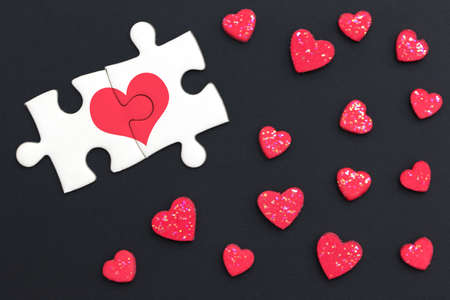 Two jigsaw puzzles painted red heart and continued on black background with many red heart. Flat lay. Valentine's day concept.