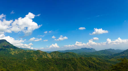 Panoramic view of summer green mountains, blue sky and white clouds. Beautiful nature landscape.