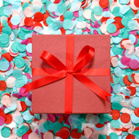 Red gift box and ribbon on colorful confetti decoration for birthday party. Flat lay. 版權商用圖片 - 121007856