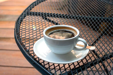 A cup of coffee on Black steel grating table in the morning.