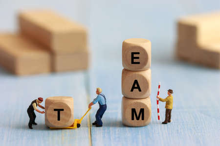 Group of miniature people assemble wooden cube, team support and help concept. Business teamwork concept. Stock Photo