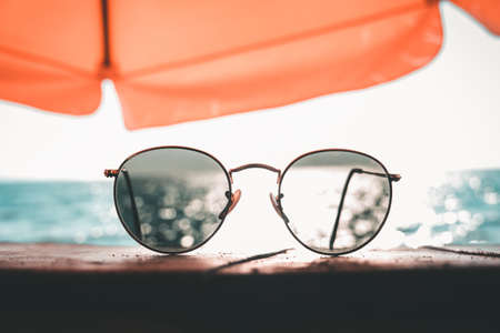 Sunglasses on the table by the sea on a chill vacation. Summer Holiday and Travel Concept