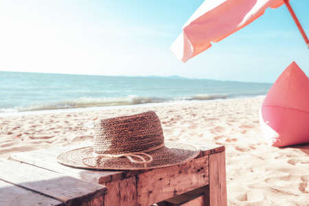 A woven hat placed on a table by the sea on a very chill holiday. Summer Holiday and Travel Concept 版權商用圖片
