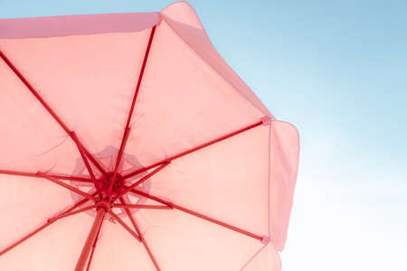 Pink umbrella against the sky on a chill vacation. Summer Holiday and Travel Concept